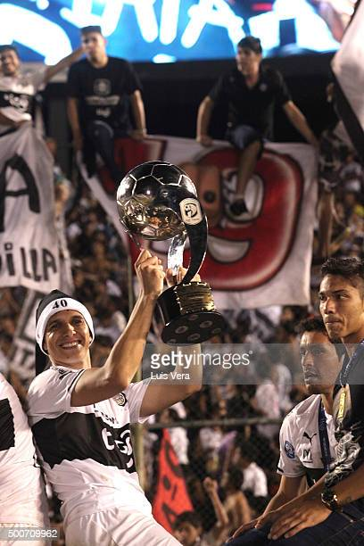Pablo Zevallos of Olimpia lifts the trophy after winning a playoff final match between Cerro Porteño and Olimpia as part of Torneo Apertura 2015 at...