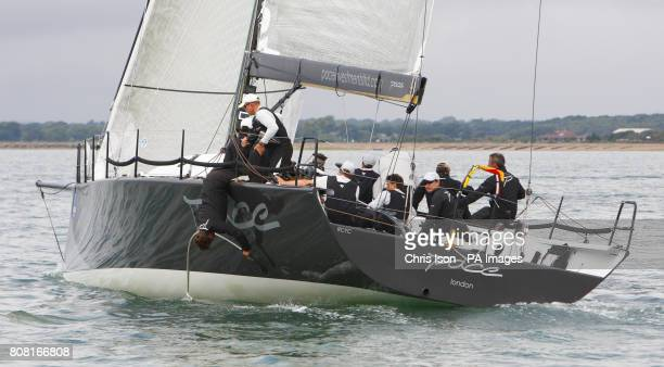Pace in the class 0 fleet continues racing as two crew members try to untangle something from under the waterline on the first day of Cowes Week Isle...
