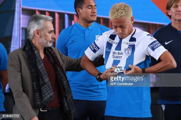 Pachuca's new footballer Japanese Keisuke Honda puts his new jersey on next to the team's president Jesus Martinez during his official presentation...