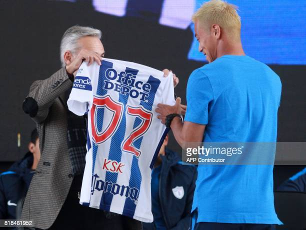 Pachuca's new footballer Japanese Keisuke Honda receives his new jersey from the team's president Jesus Martinez during his official presentation at...