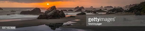 Pacific coast sunset golden sun over dramatic Oregon beach panorama