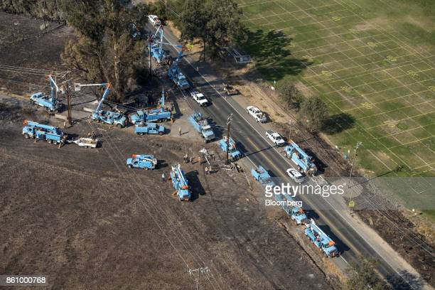 Pacific Gas Electric Co employees work to fix downed power lines burned by wildfires in this aerial photograph taken above Santa Rosa California US...