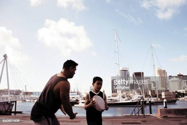 Pacific Island Man and Boy Plays Rugby against a Cityscape Harbour, in Blurred Motion