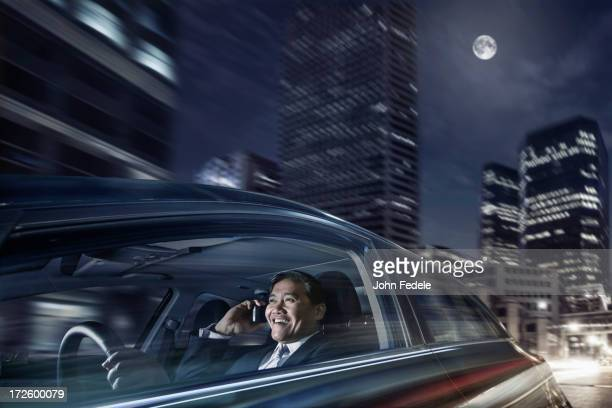 Pacific Islander businessman driving on cell phone