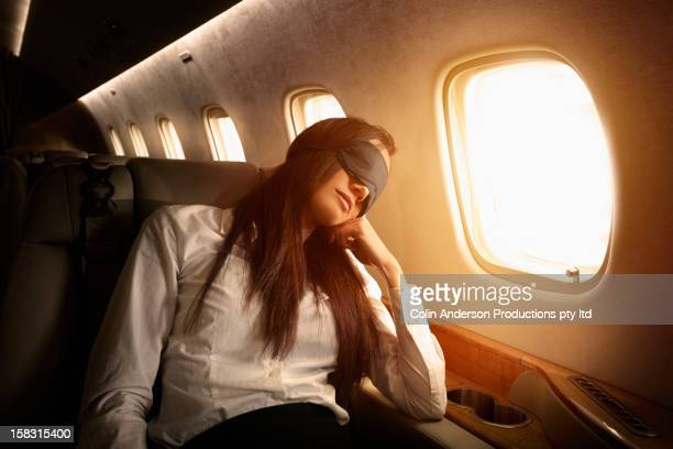 Pacific Islander businesswoman sleeping on private jet