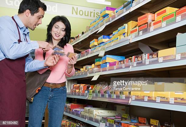Pacific Islander clerk assisting women in grocery store