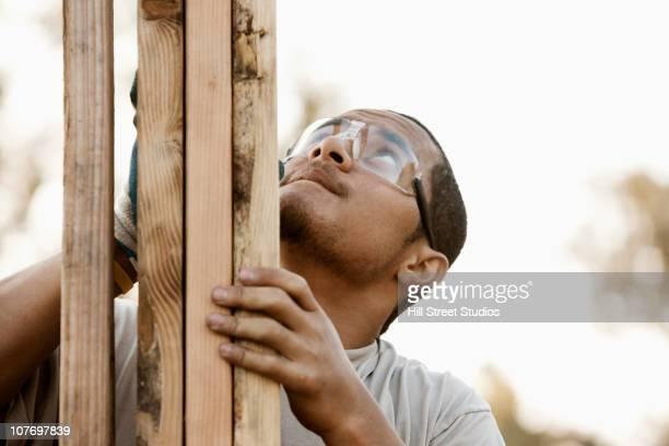 Pacific Islander construction worker adjusting house frame
