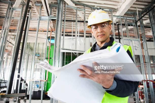 Pacific Islander construction worker reading blueprints