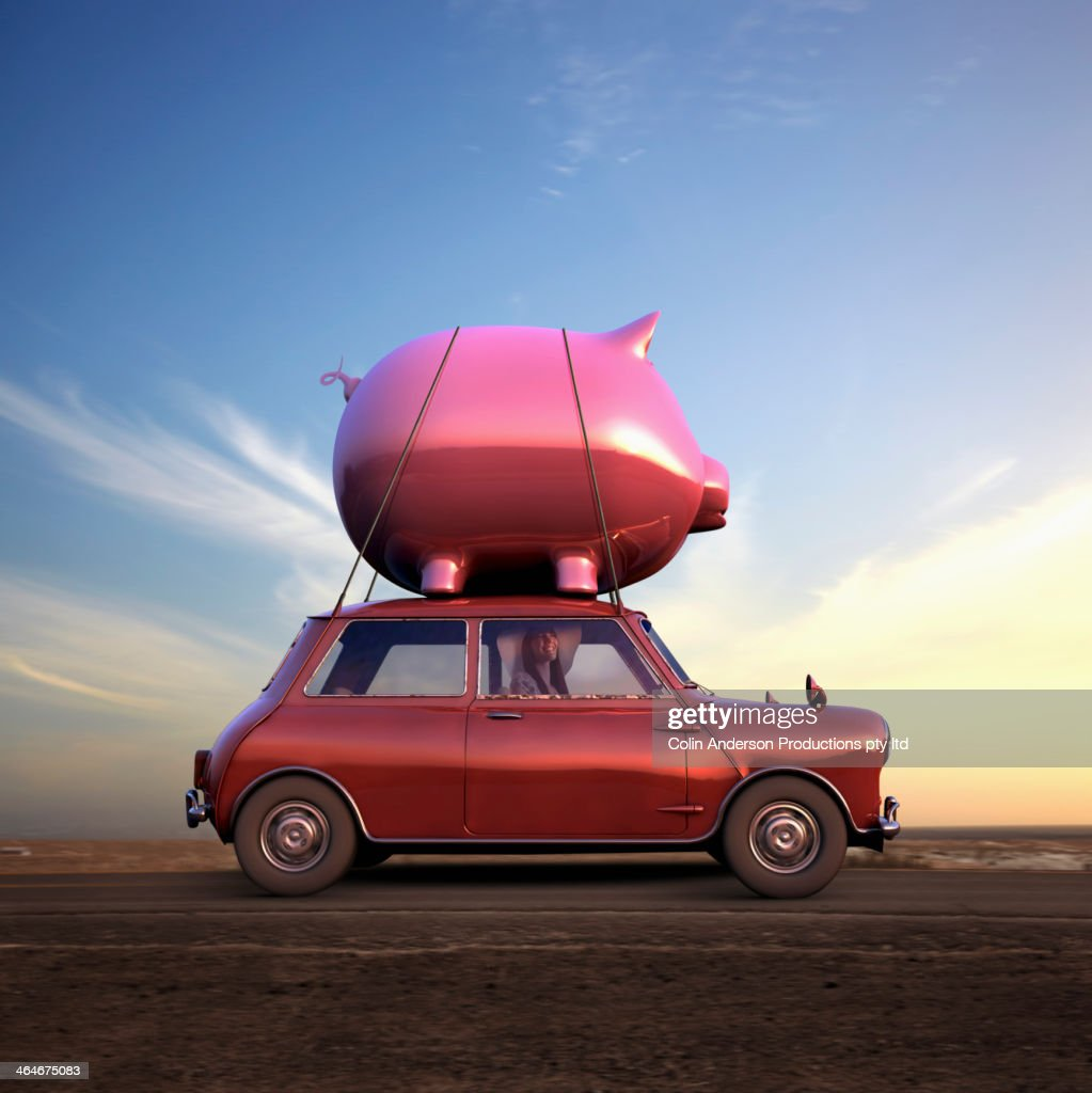 Pacific Islander driving car with piggy bank on top : Stock Photo