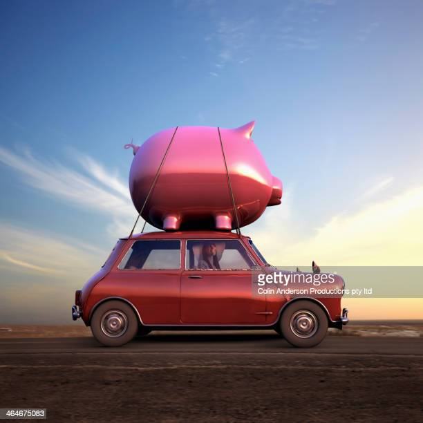Pacific Islander driving car with piggy bank on top