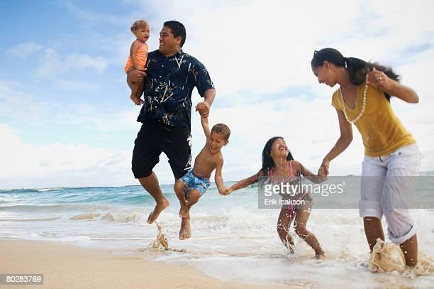 Pacific Islander family jumping in ocean surf