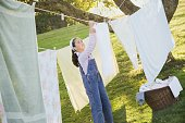 Pacific Islander girl hanging laundry on clothesline