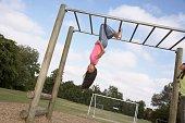 Pacific Islander girl hanging on jungle gym