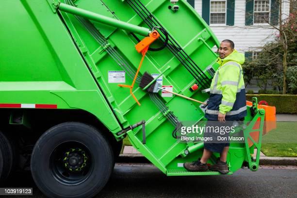 Pacific Islander man riding on garbage truck