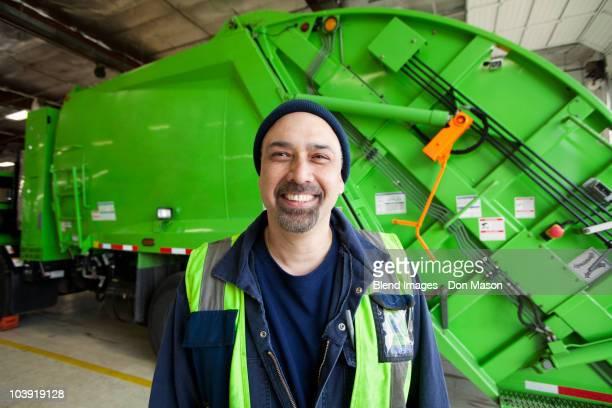 Pacific Islander man standing by garbage truck