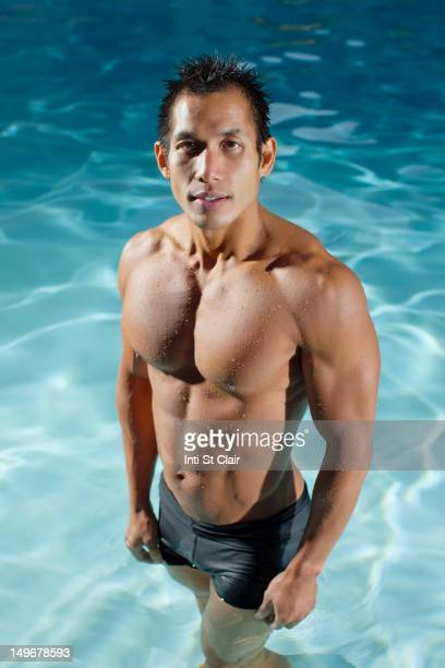 Pacific Islander man standing in swimming pool