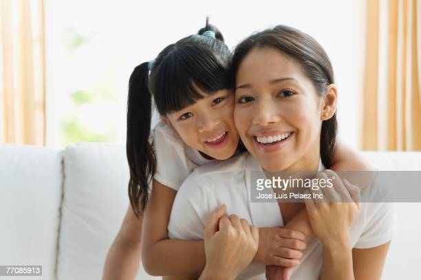 Pacific Islander mother and daughter hugging