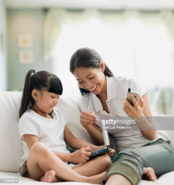 Pacific Islander mother and daughter looking at laptop