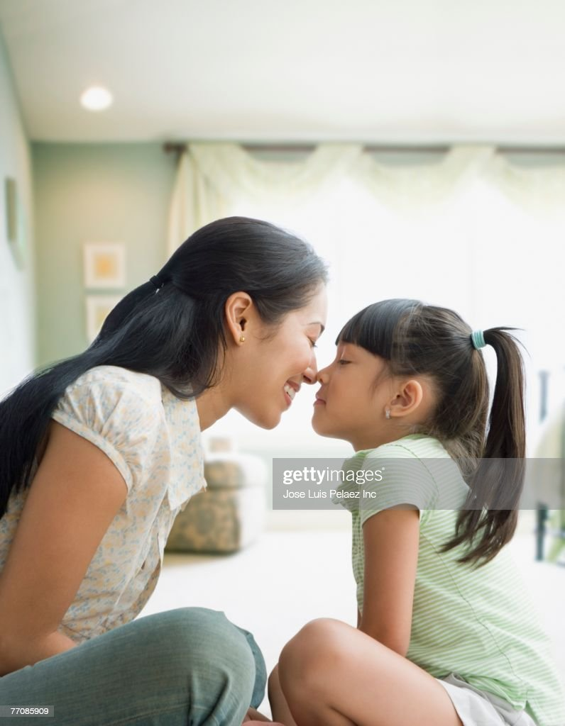 Pacific Islander mother and daughter touching noses