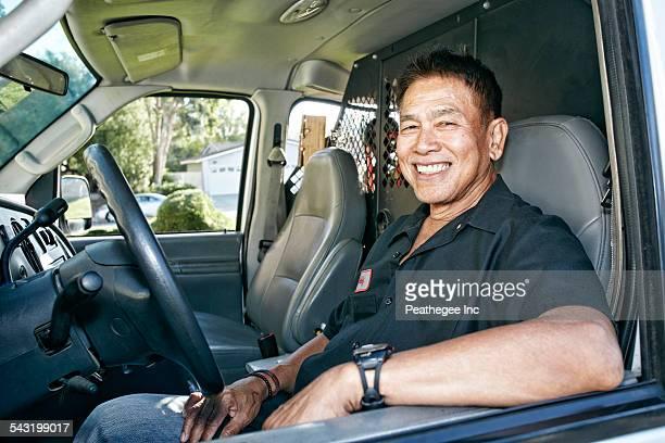 Pacific Islander plumber smiling in van