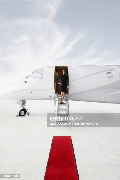 Pacific Islander stewardess standing in doorway of private jet