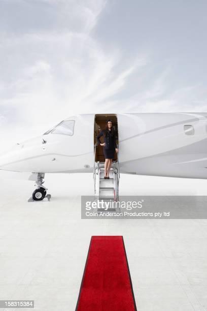 Pacific Islander stewardess standing in doorway of private jet