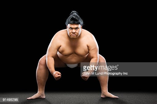 Pacific Islander sumo wrestler crouching with clenched fists : Stock Photo