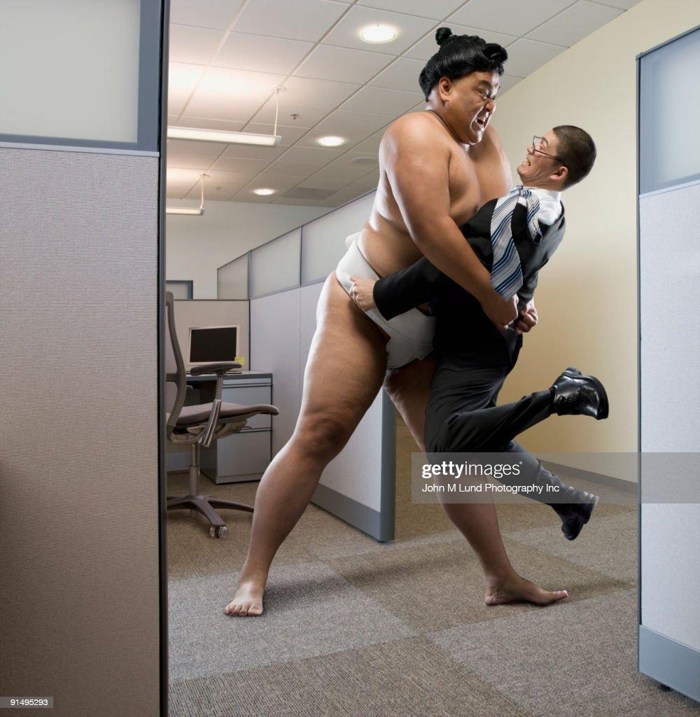 Pacific Islander sumo wrestler lifting businessman in office : Stock Photo