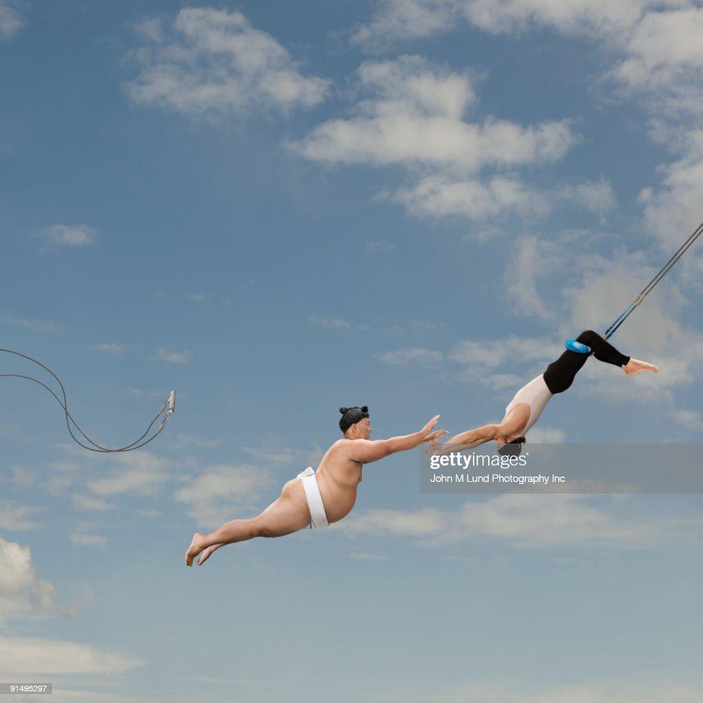Pacific Islander sumo wrestler reaching for trapeze artist
