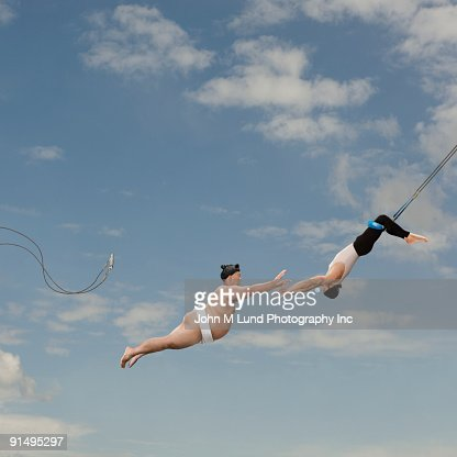 Pacific Islander sumo wrestler reaching for trapeze artist