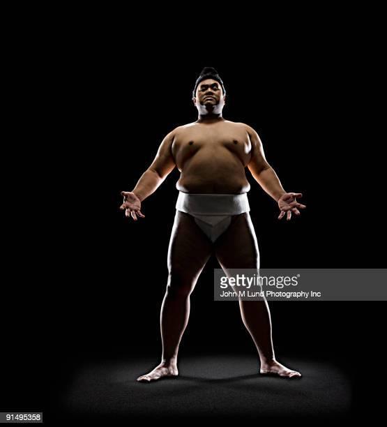 Pacific Islander sumo wrestler standing with open hands