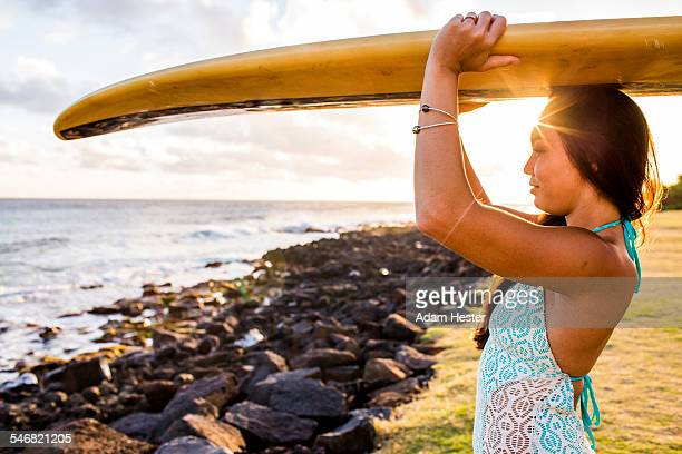 Pacific Islander surfer carrying surfboard on rocky beach