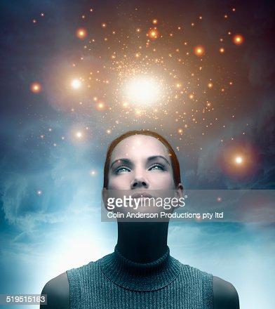 Pacific Islander woman admiring glowing lights in sky