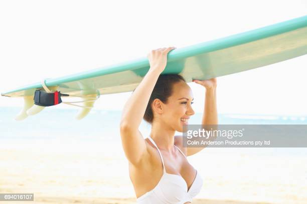Pacific Islander woman balancing surfboard on head