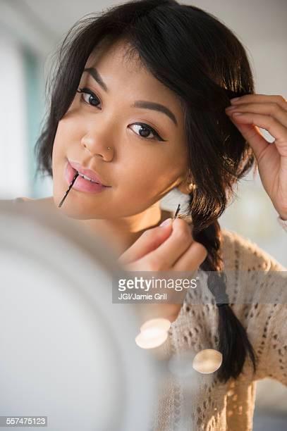 Pacific Islander woman braiding her hair