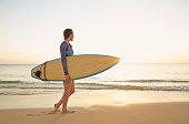 Pacific Islander woman carrying surfboard on beach