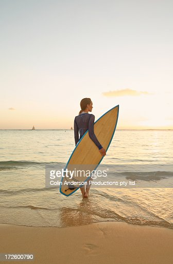 Pacific Islander woman carrying surfboard on beach : Stock Photo