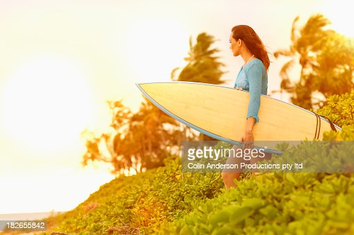 Pacific Islander woman carrying surfboard outdoors : Stock Photo