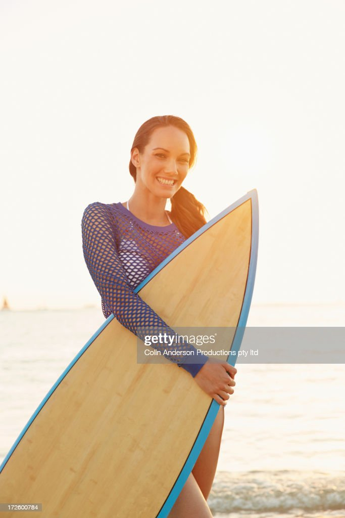 Pacific Islander woman carrying surfboard : Stock Photo