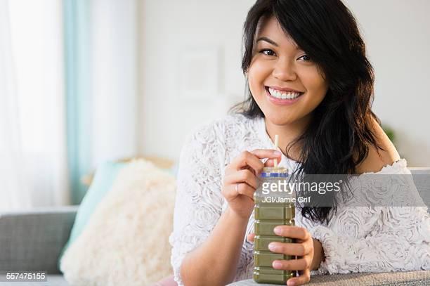 Pacific Islander woman drinking green juice