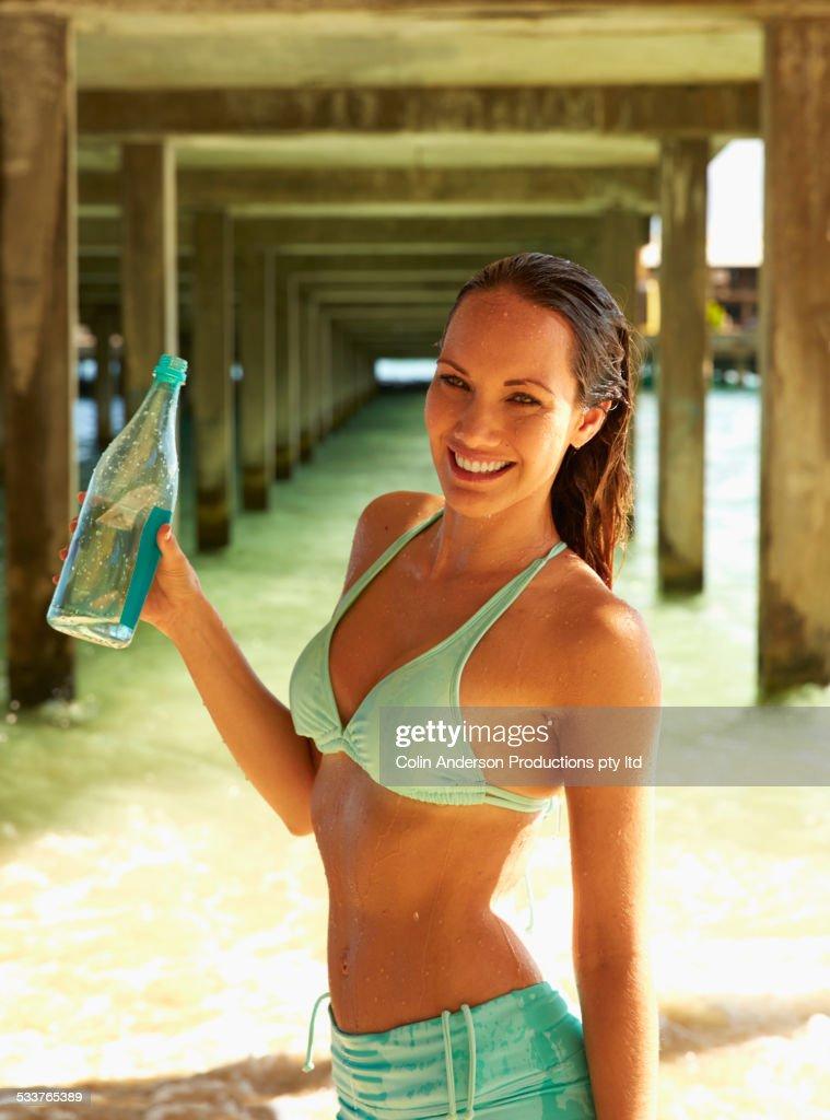 Pacific Islander woman drinking water under wooden pier on beach : ストックフォト