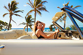Pacific Islander woman driving convertible at beach
