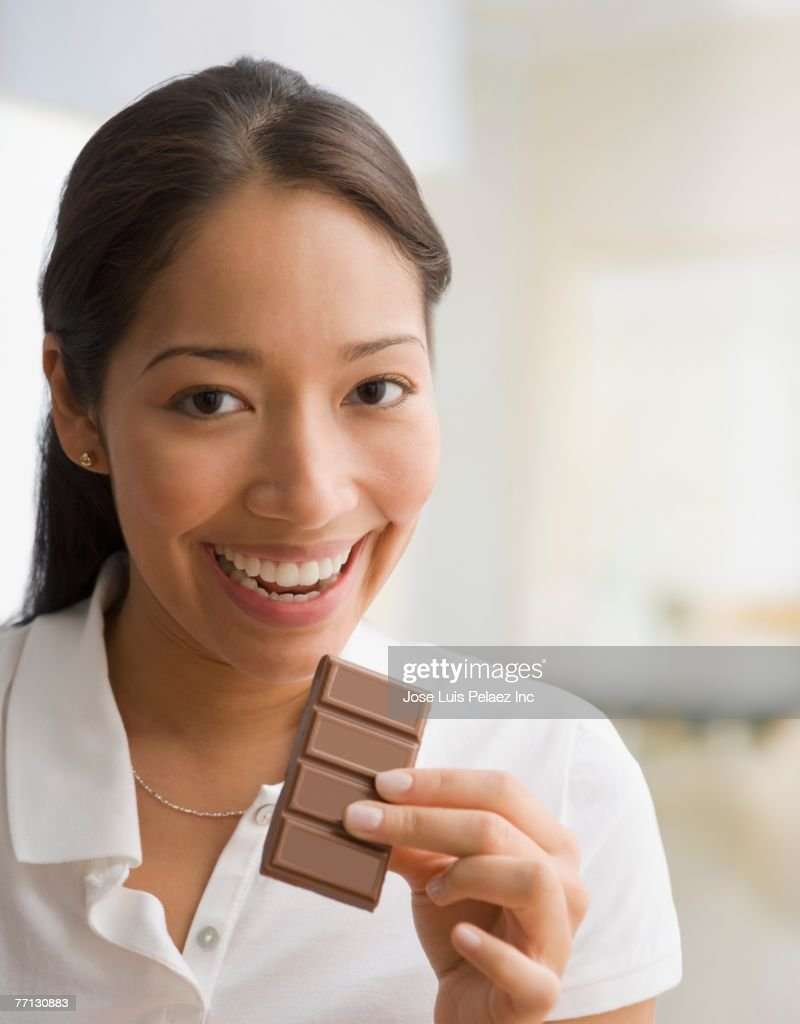 Pacific Islander woman eating chocolate : Stock Photo