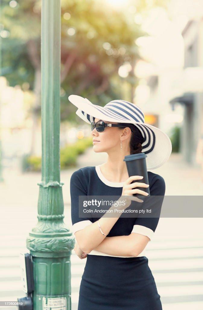 Pacific Islander woman having coffee on city street : Stock Photo