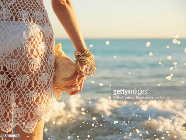 Pacific Islander woman holding conch shell on beach