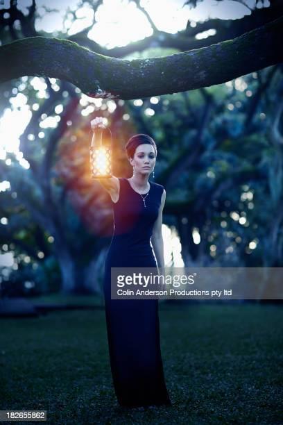 Pacific Islander woman holding lantern outdoors