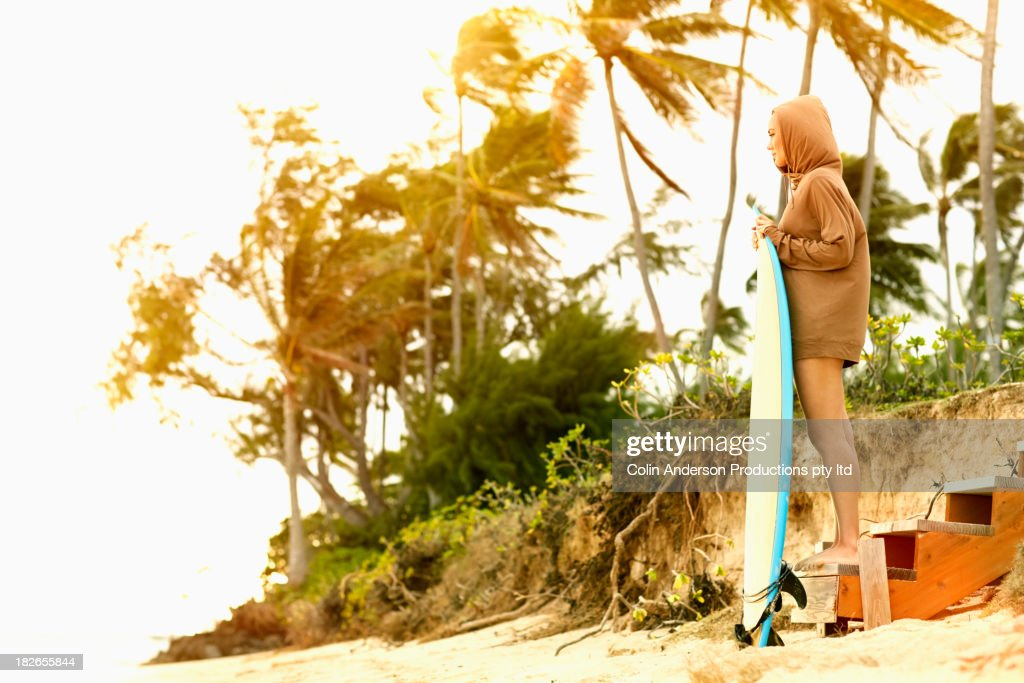 Pacific Islander woman holding surfboard on tropical beach : Stock Photo