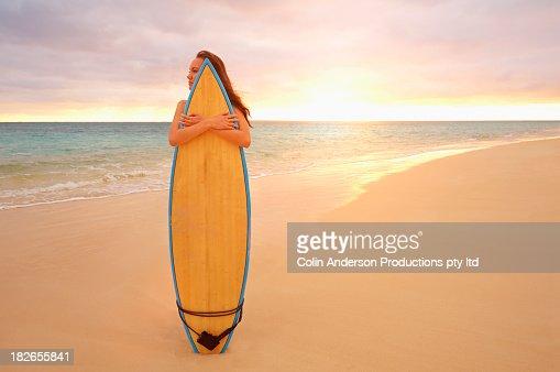 Pacific Islander woman hugging surfboard on tropical beach