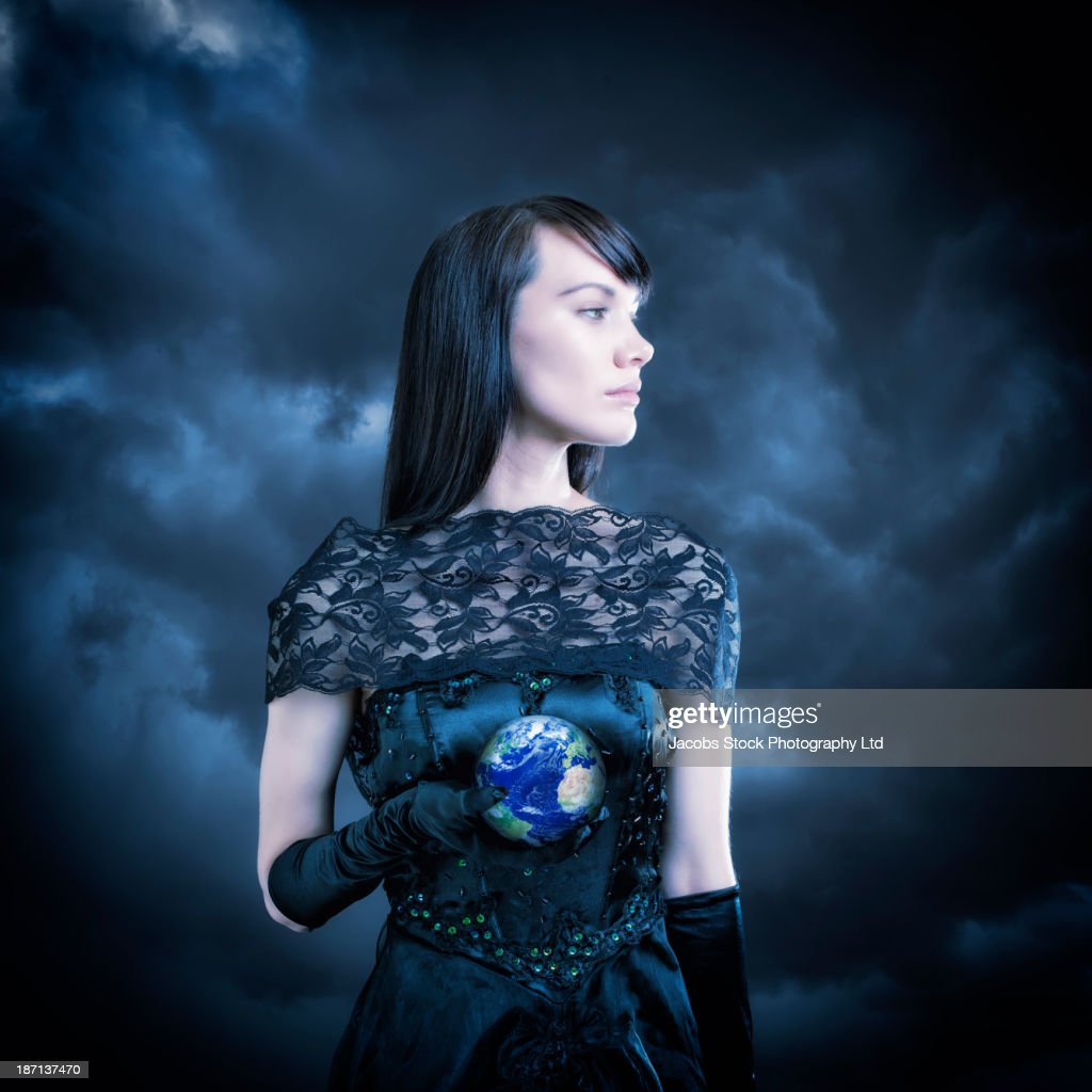 Pacific Islander woman in black gown holding globe