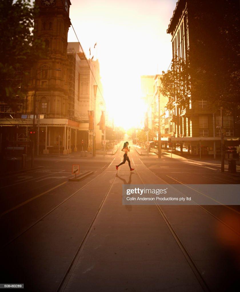 Pacific Islander woman jogging at sunset : Stock Photo